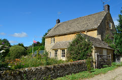 English cottage with garden. A honey-coloured Cotswold stone English cottage with a garden full of flowers and a British flag in Upper Slaughter, Cotswolds, UK Royalty Free Stock Photography
