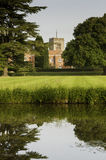English country estate. Landscaping and grounds of a wealthy English country estate including a wet moat, lawn and chapel belfry Royalty Free Stock Photo