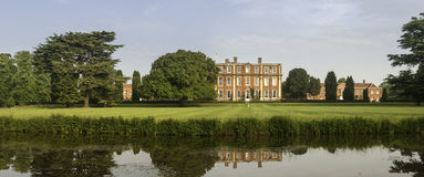English country estate. Panorama of landscaping and grounds of a wealthy English country estate including a wet moat, lawn and mansion Royalty Free Stock Photography