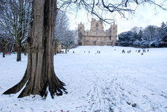 English Country Estate in Snow. View of a typical English country estate in Winter Time with people playing in the snow in the distance stock image