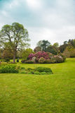 English country formal garden. Country estate garden surrounded by ornamental trees shrubs lawns and woodland. Killerton house Stock Image
