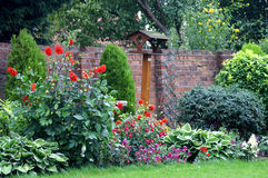 English Country Garden. Pretty English country garden in bloom featuring brick wall, bird platform and boarder Royalty Free Stock Photos