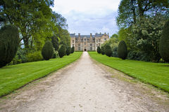 English country home in somerset. Country home at end of long drive through wooded estate and formal lawned borders  surrounded by ornamental trees and shrubs Stock Image