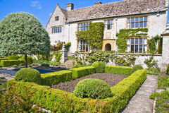 English country home in somerset. Country home and crazy paved footpath through ornamental trees and lawned and walled gardens Stock Photo
