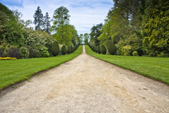 English country home in somerset. Looking away from the house down the long gravel drive through wooded estate and formal lawned borders  surrounded by Stock Photography