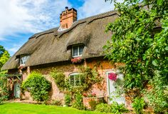 English country house with thatch roof. A traditional English country house with thatch roof. Brick house with flowers and green tree btanches. Small rustic home royalty free stock photos