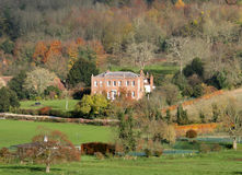 English Country Mansion. Autumn over an English Country Manor with fields and meadows in the foreground and Autumn Trees behind Royalty Free Stock Photos