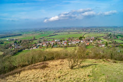 An English Country Village Down The Hill. A hilltop view down on a country village surrounded by fields Royalty Free Stock Photography