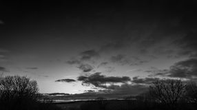 English Countryside Landscape. An evening skyline over a dark silhouette of trees Royalty Free Stock Images