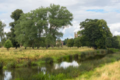 English countryside stream with cathedral in distance Royalty Free Stock Images