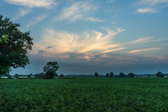 English countryside at sunset. A green field with an interesting sky while the sun is going down behind a cloud Stock Photo