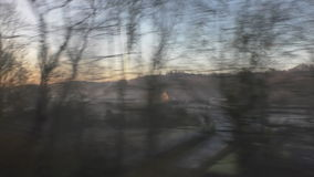 English countryside through train window. Morning frost view at dawn in rural England from moving train stock video footage