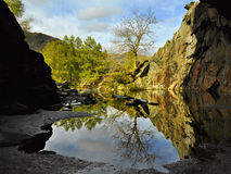 English countryside: view out of cave with pond. English countryside landscape taken in Lake District, North Yorkshire, looking out of a wet cave with puddles Stock Photo