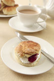 English cream tea. A traditional English cream tea, with scones, strawberry jam and whipped cream, served with tea and milk Royalty Free Stock Photography