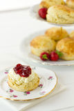 English cream tea, vertical. English Cream tea scene with scones, Devonshire style, on china plate with cake stand behind. Part of a series showing the Stock Photography