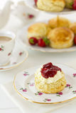 English cream tea, vertical. English Cream tea scene with scones, Devonshire style, on china plate with teacup and saucer. Part of a series showing the Royalty Free Stock Photo