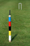 An English croquet lawn, the focus on the centre peg. The far hoop out-of-focus Royalty Free Stock Images
