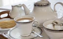 An English cup of tea. With saucer, tea pot and biscuits Stock Image