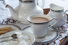 An English cup of tea. With saucer, tea pot, sugar cubes and biscuits Stock Photos