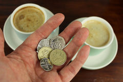 English Currency in hand with two coffee  in background. Royalty Free Stock Photo