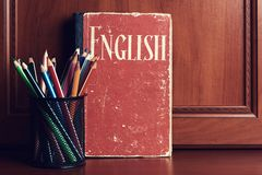 English dictionary with pencils on a wooden table stock photos