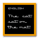 English education black board. A school chalk black board or blackboard with the words english and the words the cat sat on the mat chalked on it with a tan Royalty Free Stock Photography