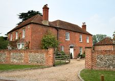 English Farmhouse. English Red Brick Farmhouse in Rural England with a Brick and Flint surrounding wall Royalty Free Stock Image