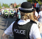 English Female Police Officer. An English female Police Officer with motorcycle Police in the background, Policing an event (London 2012 Olympic Torch procession Royalty Free Stock Image