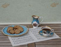 English teacup with saucer, cream jug and a cake plate with cookies, fine bone china porcelain, on a sheet of music royalty free stock images