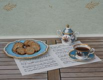 English teacup with saucer, sugar bowl and a cake plate with cookies, fine bone china porcelain, on a sheet of music stock images