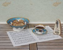 English teacup with saucer and a cake bowl with cookies, fine bone china porcelain, and a metronome for music on a sheet of music. English fine bone china stock photos