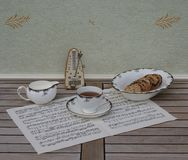 English teacup with saucer, cream jug  and a cake bowl, fine bone china porcelain, and a metronome for music on a sheet of music stock photo