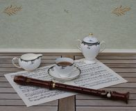 English teacup with saucer, cream jug and sugar bowl, fine bone china porcelain, and a block flute on a sheet of music. English fine bone china Porcelain with stock photography