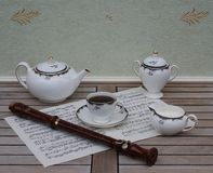 English teacup with saucer, teapot, cream jug and sugar bowl, fine bone china porcelain, and a block flute on a sheet of music. English fine bone china Porcelain stock images