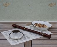 English teacup with saucer and a cake bowl and a block flute on a sheet of music royalty free stock photography