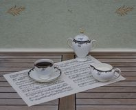 English teacup with saucer, cream jug and sugar bowl, fine bone china porcelain, on a sheet of music. English fine bone china Porcelain with hand painted floral royalty free stock image