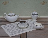 English teacup with saucer, teapot, cream jug and sugar bowl, fine bone china porcelain, on a sheet of music. English fine bone china Porcelain with hand painted stock images