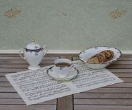 English teacup with saucer, sugar bowl and a cake bowl with cookies, fine bone china porcelain, on a sheet of music stock photo