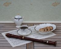 English teacup with saucer, sugar bowl and a cake bowl, fine bone china porcelain, and a block flute on a sheet of music. English fine bone china Porcelain with stock photos
