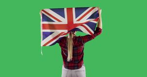 English flag on the back of a woman on chroma key green screen. Female model raises the British flag up. Flag of Great Britain fluttering in the wind stock footage