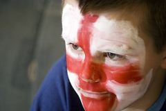 English flag on boys face. Portrait of young boy with English George cross painted on face Stock Image