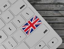 English flag enter key on white keyboard, on wood background. 3d render. Illustration royalty free stock images