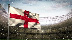 English flag waving in the snow in full arena. Digital composite of a English flag waving in the snow with a filled open arena and blue cloudy sky in the stock video