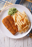 English food: fried fish in batter with chips close-up. vertical Royalty Free Stock Photos
