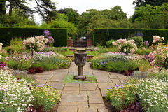 English formal garden. Flagged garden with a stone vase ornament and summer flowers Stock Photo