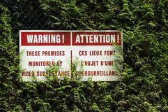 English and French surveillance warning sign with red lettering hung in hedge. stock photo