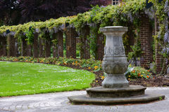 English Garden. Fountain and flowers in an English manicured garden stock images