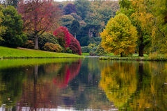 English Garden. With autumn colours an reflection of trees in lake royalty free stock image