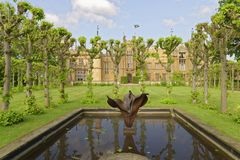 English garden, knebworth house, england. pruned. Image taken of a stately home protected by neatly pruned trees and a pond in knebworth house, hertfordshire stock images