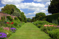 English garden with old wall and gates. Wall garden with topiary shrubs in an English Stately Home Stock Photo
